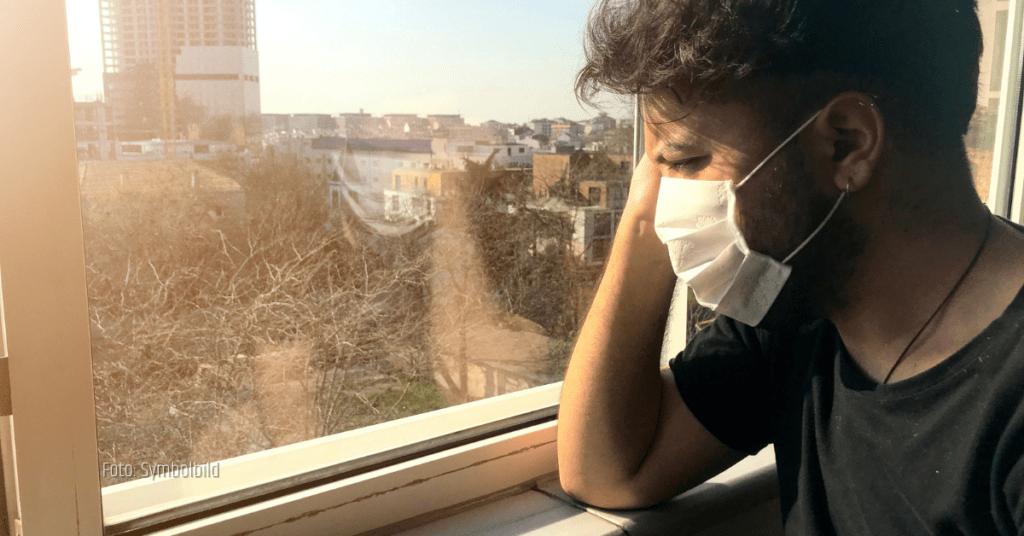 Ein Mann steht während der Corona-Pandemie in seiner Wohnung beim Fenster. Er trägt eine Maske und schaut sehnsüchtig nach draußen.