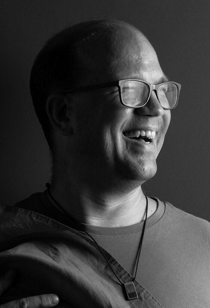 Schwarz-Weiss Bild von Frank Thiess, der lacht und nach rechts schaut.