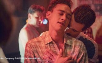 Ein Mann umarmt Richie von hinten und küsst ihn im Genick